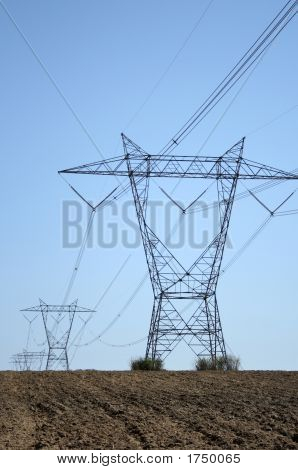 Electricity Pylons In Ploughed Land