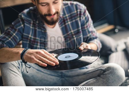 Young smiling man in checkered shirt holding vinyl record