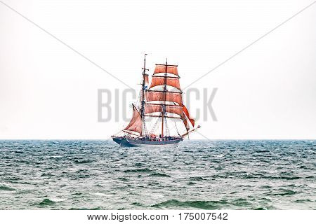 Sailing ship with red sails on the sea. Tall Ship.Yachting and Sailing travel. Cruises and holidays. Postcard and Book cover.