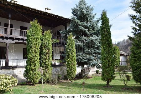 Beautiful arranged garden to an old monastery building. Clean Sky. In the garden sort trees, trees, cypresses