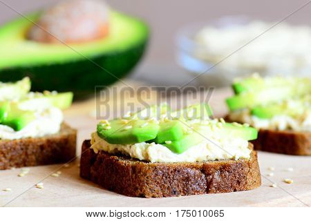 Vegetarian avocado and hummus sandwiches on a wooden board. Half avocado, hummus in a glass bowl. Simple and healthy open sandwiches. Meatless food. Closeup
