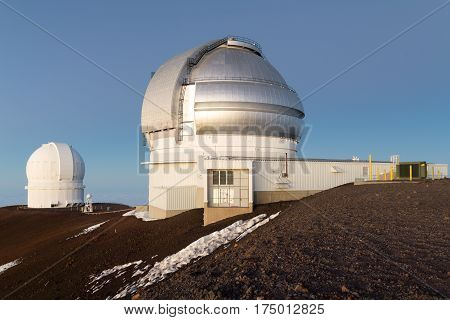 The Canada-France-Hawaii and Gemini Observatories against blue sky at dusk on Mauna Kea.