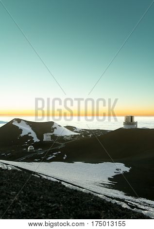 Mauna Kea Observatory telescopes above the clouds at sunset in winter with snow on the cinder foreground.