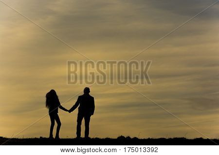 Silhouette of two people before the sundown. Silhouette of couple holding hands and looking on each other with love.
