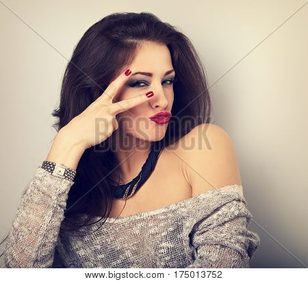 Grimacing Female Model Showing Rock V-sign Gesture In Fashion Necklace. Bright Makeup And Red Lipsti
