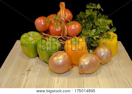 Fresh vegetables : red garden tomatoes, green peppers, yellow peppers, parsley, red onion put on small wicker basket on light wood table on black background