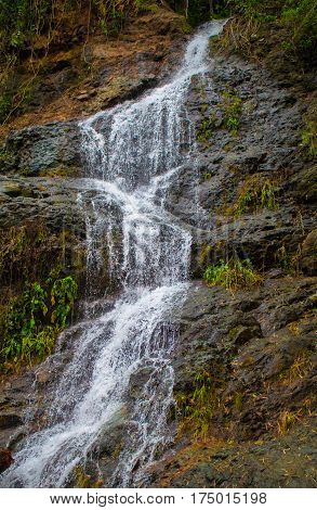 Tall waterfall on mountain. Waterfall stream detailed photo. Fresh cold waterfall on mossy rocks. Untouched natural environment of Philippines. Wet stones under white water. Rainy season in tropics