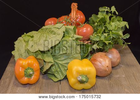 Fresh vegetables : red garden tomatoes, lettuce,parsley, yellow peppers, parsley, red onion put on small wicker basket on dark wood table on black background