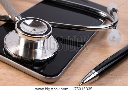Stethoscope and pen on smartphone checking healthcare security. Stethoscope on smartphone checking security on smartphone. Doctor contact or appointment concept.