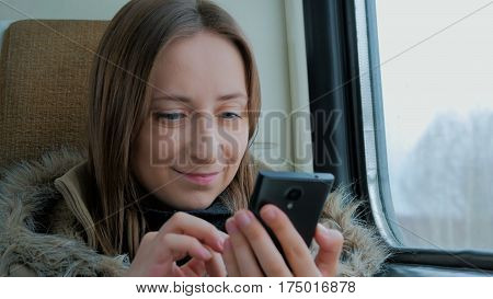 Close up shot. Pensive woman traveling on a train and using a smartphone. Travel, transport and technology concept