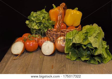 Fresh vegetables : red garden tomatoes, lettuce yellow peppers, parsley, red onion,cut in twain red onion put in small wicker basket put on dark wood table on black background