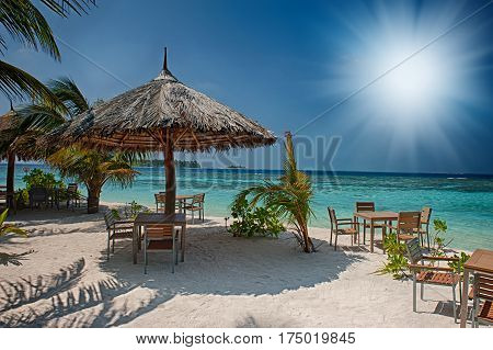 Tropical island with palm trees and amazing vibrant beach in Maldives. White parasol in sea tropical Maldives romantic atoll island paradise luxury resort about coral reef. Umbrella on a beach