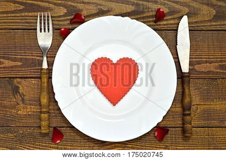 Valentines Day table decoration: Plate with heart ornament, silverware and rose petald