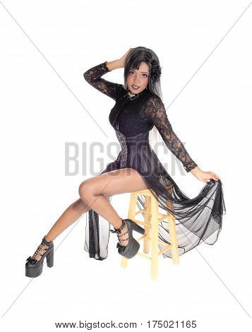 A beautiful African American woman sitting in a black corset and twill skirt isolated for white background.
