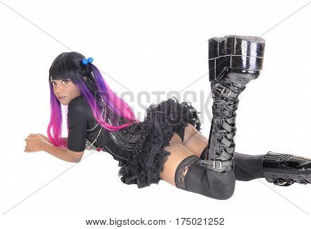 A young steampunk African American woman in a short skirt and long boots lying on the floor isolated for white background.