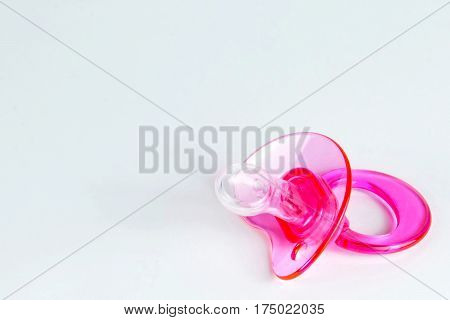 Close up of pink baby soother on light background