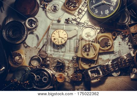 Close up shot of some watches and tools at a repair shop.