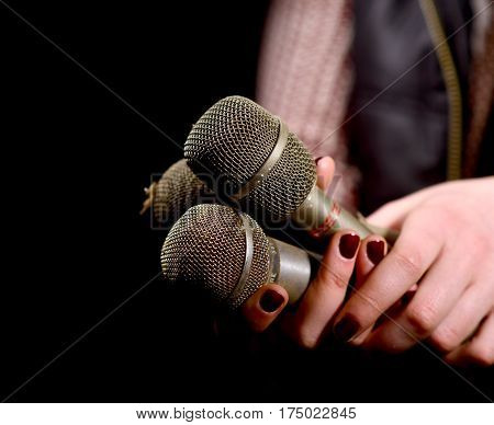 Woman Hands Holding Dirty And Dusty Microphone On A Dark Background