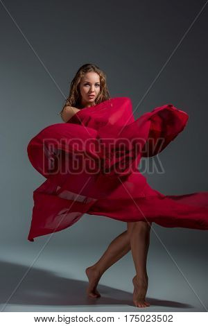 Young beautiful dancer in red dress posing on a dark gray studio background. Modern, Contemporary, improvisation
