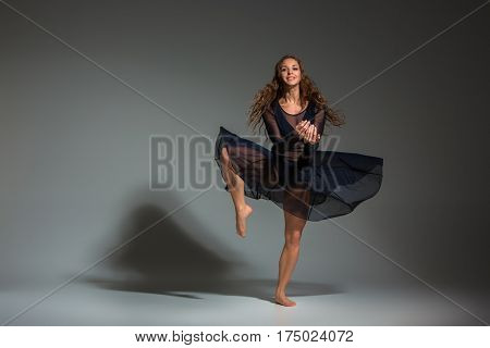 Young beautiful dancer in black dress posing on a dark gray studio background. Modern, Contemporary, improvisation