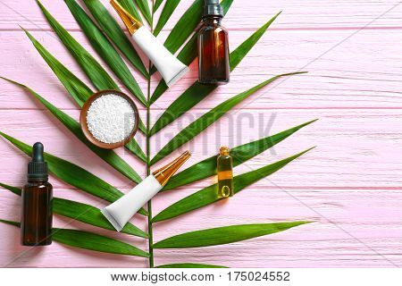 Cosmetic with green leaf on wooden background