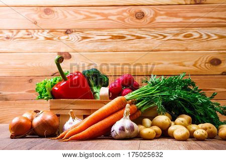 Vegetables. Potatoes, carrot and red pepper. Garlic, onion and brocoli. Lettuce salad and red radish. Wooden basket on planks background.