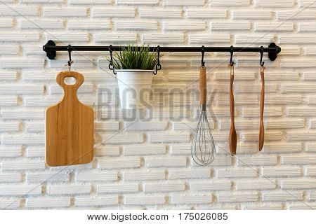 Wooden Cookware On Kitchen Brick Wall