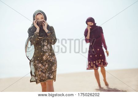 Desert women thirsty dehydrated tired walking outdoors. Dehydration, overheating, thirst and heat stroke concept image with two sisters in desert nature. Beautiful mixed race asian caucasianl arabian girls lost in desert during journey.