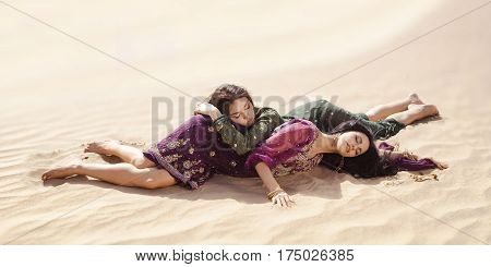 Desert women lying on sand outdoors. Dehydration, overheating, thirst and heat stroke concept image with two sisters outdoors in the nature. Two arabian girls lost in desert during journey.