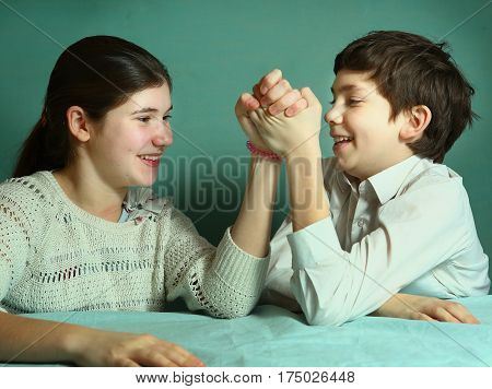 siblings teenager brother and sister arm wrestling close up smiling photo poster