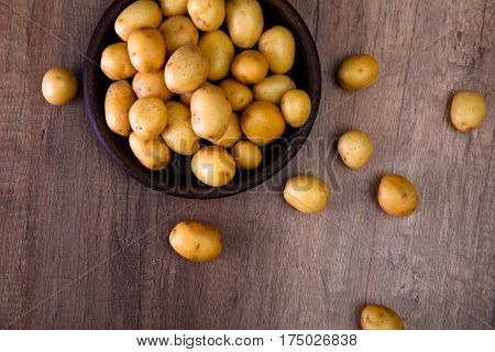 Potatoes in a rustic plate. Raw new potato. Fresh natural vegetables. Organic bio food on wooden table.