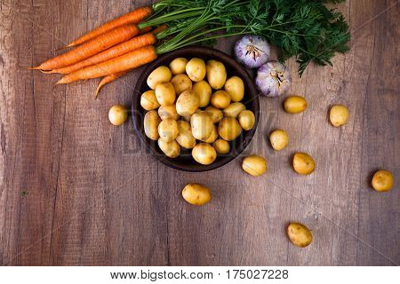 Potatoes in a rustic plate. Carrot, garlic and raw new potato. Fresh natural vegetables. Organic bio food on wooden table.