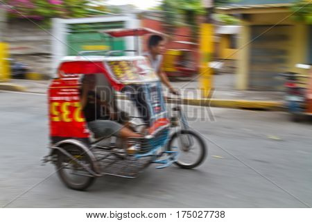 Panning photograph of unidentified man riding Tricycle Taxi. They are often seen in city area where public transportation services are insufficient and most residents can't afford high commuting costs Philippines