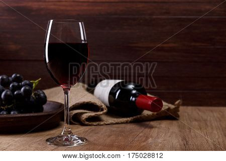 Red wine. Bottle with wineglass. Dark grapes branch on plate. On rustic wooden background.