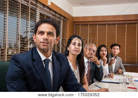 Group Of Indian Businesspeople In Video Conference or at presentation or listening to a sales speech At Business Meeting, with a miniature indian flag post over table