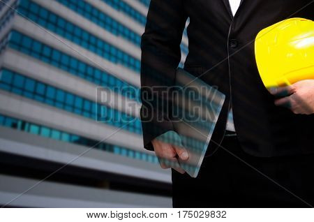 double exposure of professional engineer hold in hand yellow safety helmet and laptop business and industrial concept on building business district city background, color tone effect, copy space.