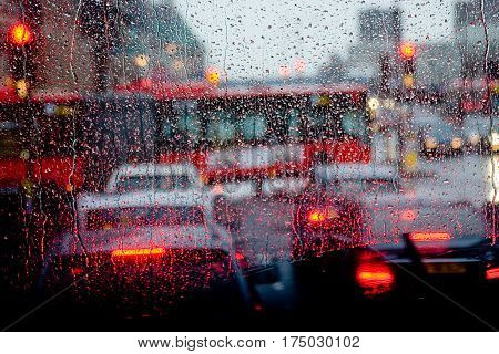 London rain view to red bus through rain-specked window