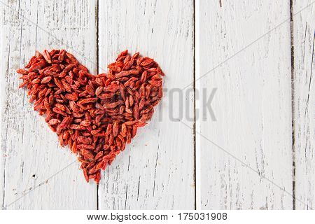 Goji berries as a heart on old white wooden table, top view.