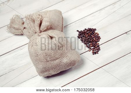 Coffee beans with burlap sacks on white wooden table