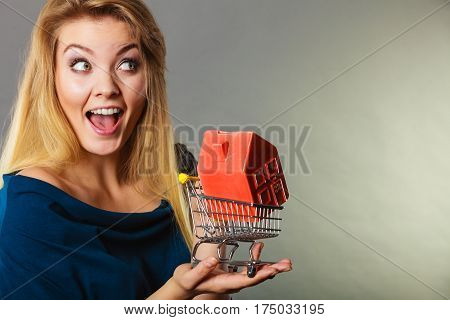 Woman Holding Shopping Cart With House Inside