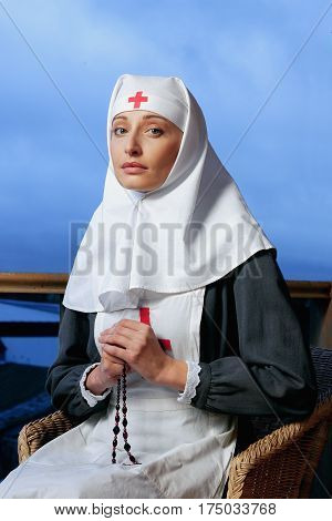 MOSCOW RUSSIA - OCTOBER 10.2004: young nun nurse sitting in a chair with rosary