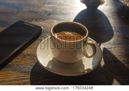 freshly brewed hot natural coffee with crema in white Cup on a bright Sunny day on the beach