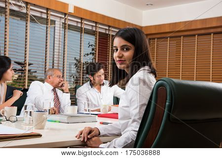 Young and beautiful indian female business executive laughing and sitting in front of her team, indian business woman in the office looking at camera