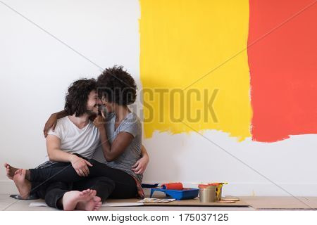 Happy young multiethnic couple relaxing after painting a room in their new house on the floor