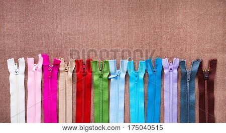Tailor: Colorful And Many Zipper For Tailoring, Sewing Brown Background