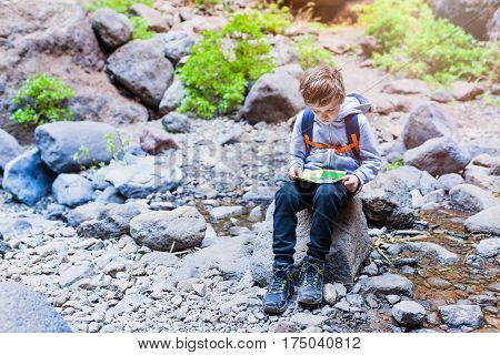 Little Boy Child Reading Map On Mountain Trail.