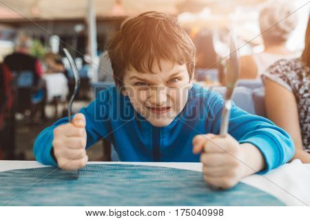 Little Child Boy Hungry Waiting For Dinner In Restaurant