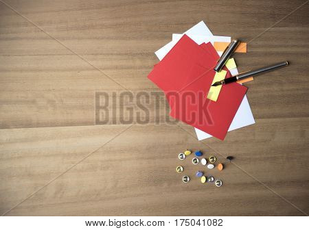 Multi coloured note paper with drawing pins and a pen on a wooden background