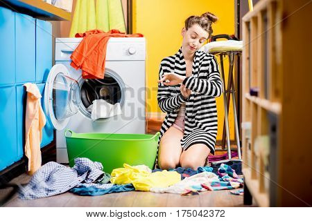 Young housewife sitting sadly near the washing machine with lots of colorful clothes on the floor at home