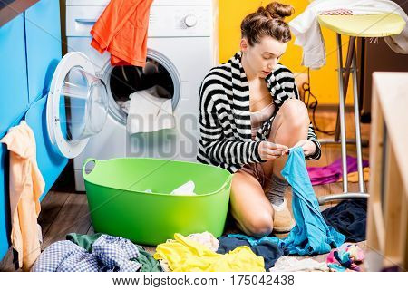 Young housewife checking the clothes sitting on the floor near the washing machine at home